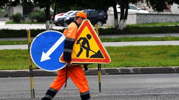 Рабочий переносит дорожные знаки во время укладки верхнего слоя дорожного покрытия