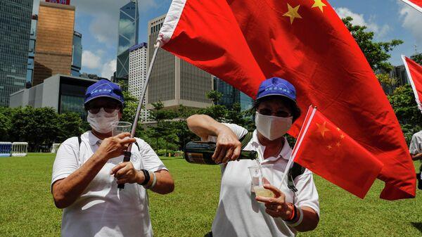 Люди с флагами празднуют принятие парламентом Китая закона о национальной безопасности Гонконга