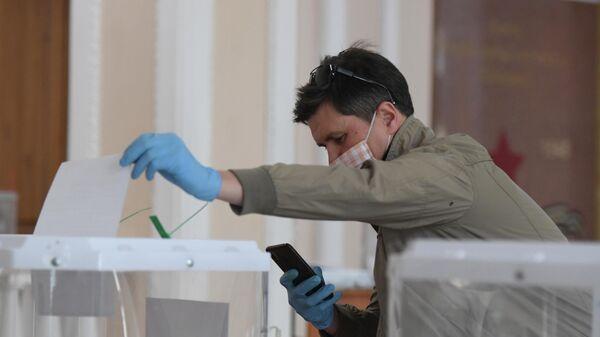 Мужчина фотографирует бюллетень во время голосования по вопросу одобрения изменений в Конституцию РФ на избирательном участке в Казани