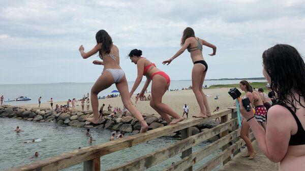 Девушки прыгают с моста в пруд в Эдгартауне, штат Массачусетс