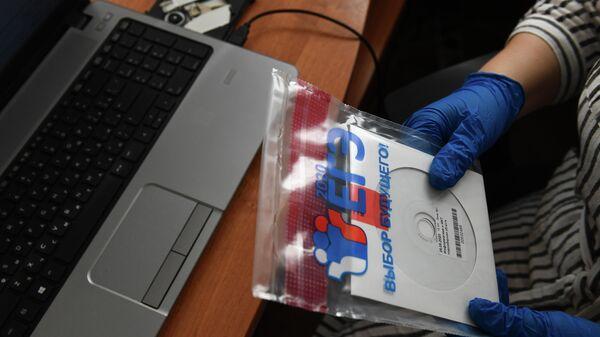 Учитель держит конверт с диском, в котором содержатся задания для ЕГЭ