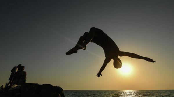 Мужчина прыгает с пирса на пляже в посёлке городского типа Новофёдоровка Сакского района