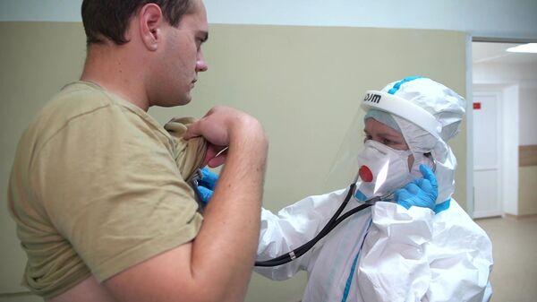 Врач проводит ежедневный обход-осмотр участника испытаний вакцины от коронавируса в Главном военном клиническом госпитале имени Н. Н. Бурденко