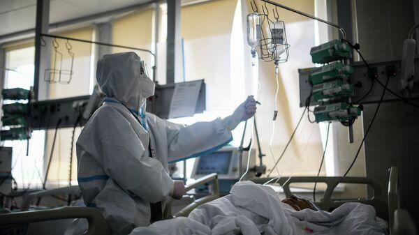 Врач проверяет капельницу у пациента в реанимации городской клинической больницы № 15 имени О. М. Филатова в Москве