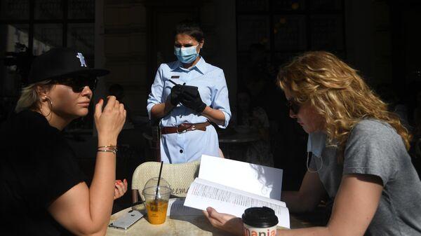 Посетительницы и официантка на летней веранде кофейни в Москве