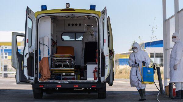 Дезинфекция автомобиля скорой помощи на территории городской клинической инфекционной больницы имени И. С. Жекеновой в Алма-Ате