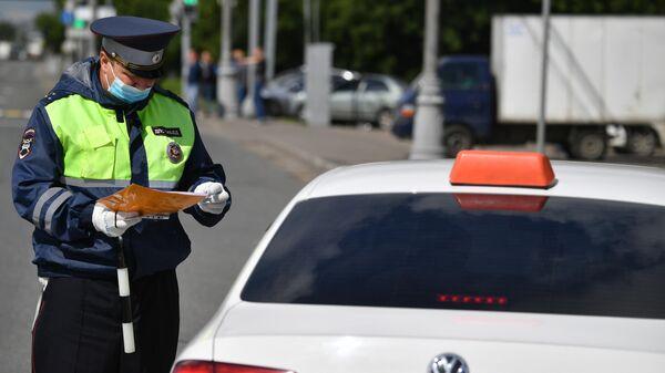 Сотрудник ГИБДД во время рейда в Москве по проверке автомобилей такси на соответствие правилам безопасности перевозок
