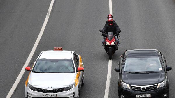 Мотоциклист двигается между рядами по проезжей части в Москве