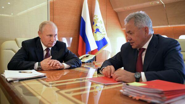 Президент РФ Владимир Путин и министр обороны РФ Сергей Шойгу  во время встречи на борту самолёта