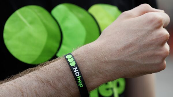 Браслет с надписью Нет гепатита во время мероприятий, приуроченных ко Всемирному дню борьбы с гепатитом в Лондоне