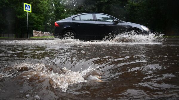Автомобиль едет по подтопленной из-за дождя дороге в Москве