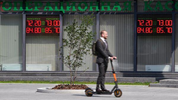 Мужчина около электронного табло с курсами валют в Москве