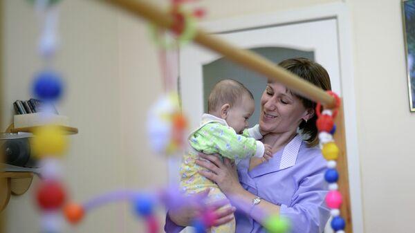 Нянечка держит на руках малыша