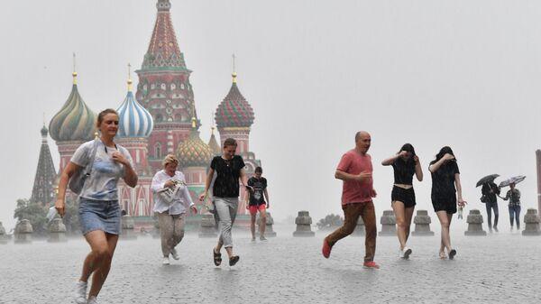 Люди во время дождя на Красной площади в Москве
