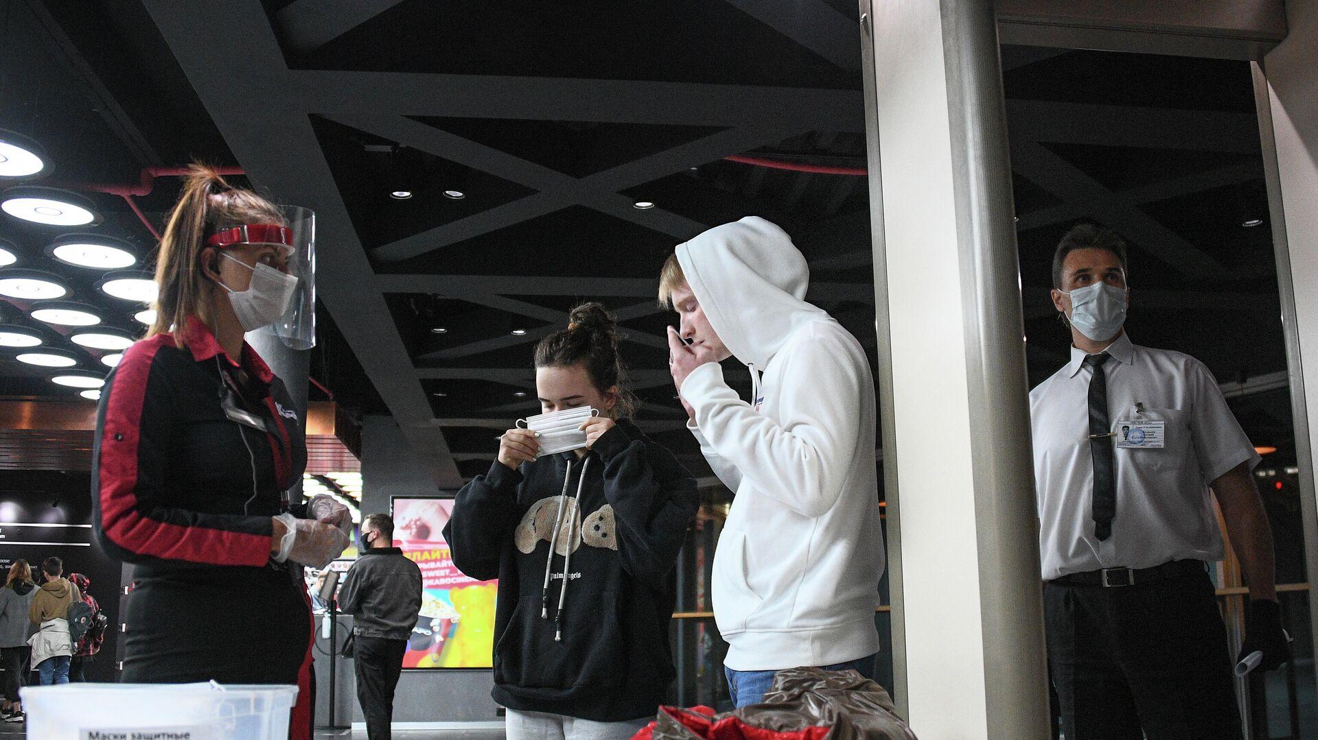 Зрители надевают защитные маски на входе в кинотеатр Каро 11 Октябрь в Москве - РИА Новости, 1920, 29.09.2020