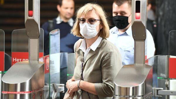 Пассажиры проходят через турникеты в Московском метрополитене