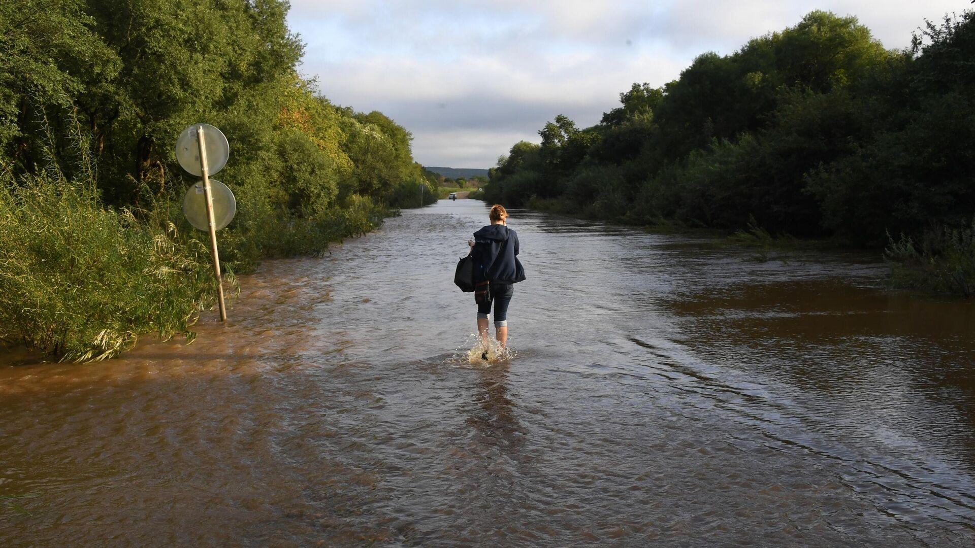 Женщина идет по затопленной паводком дороге в районе Уссурийска - РИА Новости, 1920, 11.08.2020