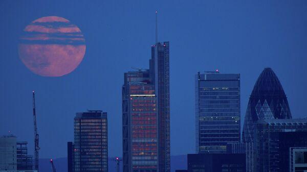 Полная луна над финансовым районом лондонского Сити в Великобритании