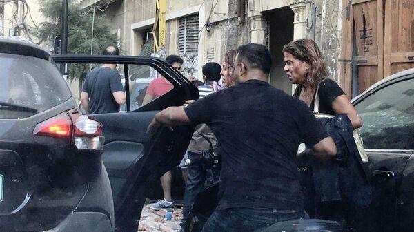 Люди, пострадавшие от осколков витрин, выбитых в результате взрыва в районе порта в Бейруте