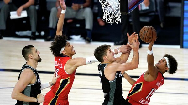 LAKE BUENA VISTA, FLORIDA - AUGUST 06: Bogdan Bogdanovic #8 of the Sacramento Kings, center right, competes for an offensive rebound against New Orleans Pelicans' Frank Jackson #15, right, and Pelicans' Jaxson Hayes #10, center left, as Kings' Alex Len #25, left, looks on during the second half of an NBA basketball game at HP Field House at ESPN Wide World Of Sports Complex on August 6, 2020 in Lake Buena Vista, Florida. NOTE TO USER: User expressly acknowledges and agrees that, by downloading and or using this photograph, User is consenting to the terms and conditions of the Getty Images License Agreement.   Ashley Landis-Pool/Getty Images/AFP