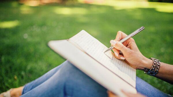 Девушка пишет в блокноте в парке