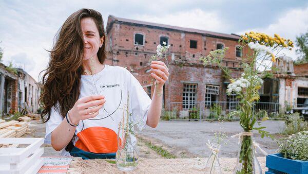 Девушка-волонтер украшает территорию проекта Лето на заводе