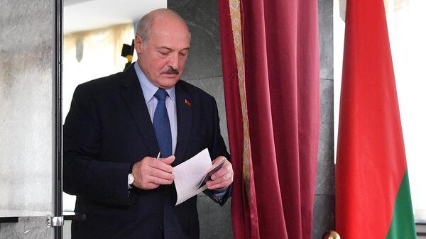 Президент Белоруссии Александр Лукашенко голосует на выборах президента Белоруссии на избирательном участке в Минске