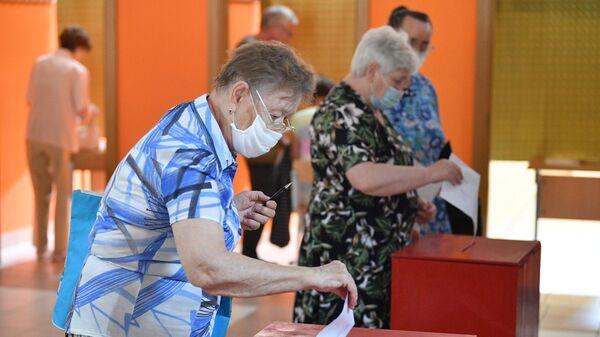 Люди голосуют на выборах президента Белоруссии на избирательном участке №20 в Минске