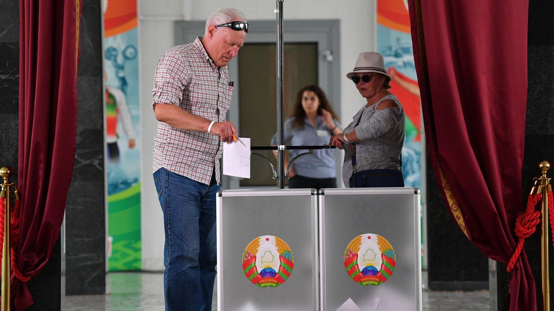 Мужчина голосует на выборах президента Белоруссии на избирательном участке в Минске - РИА Новости, 1920, 21.09.2020