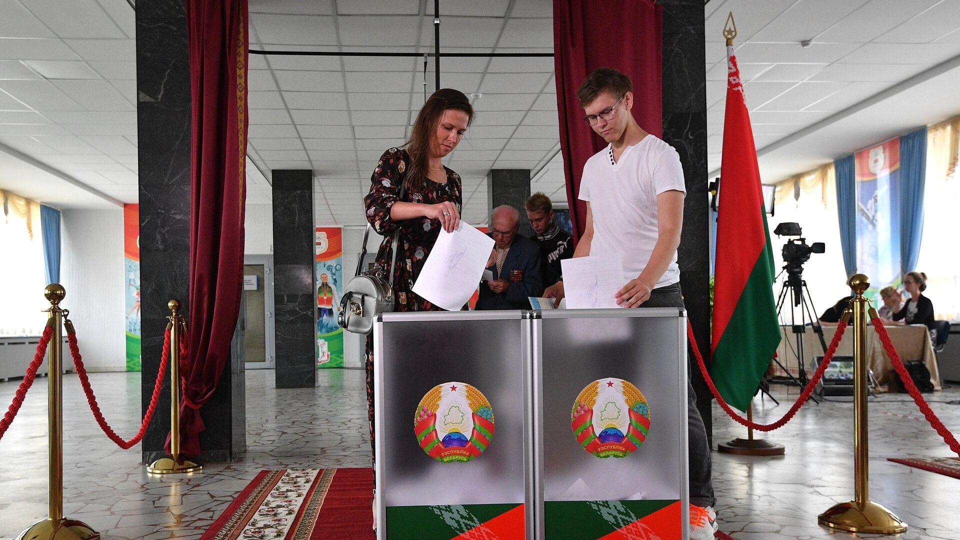Молодые люди голосуют на выборах президента Белоруссии на избирательном участке в Минске - РИА Новости, 1920, 27.04.2021