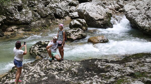 Туристы фотографируются у реки Курджипс в Гуамском ущелье в Краснодарском крае.