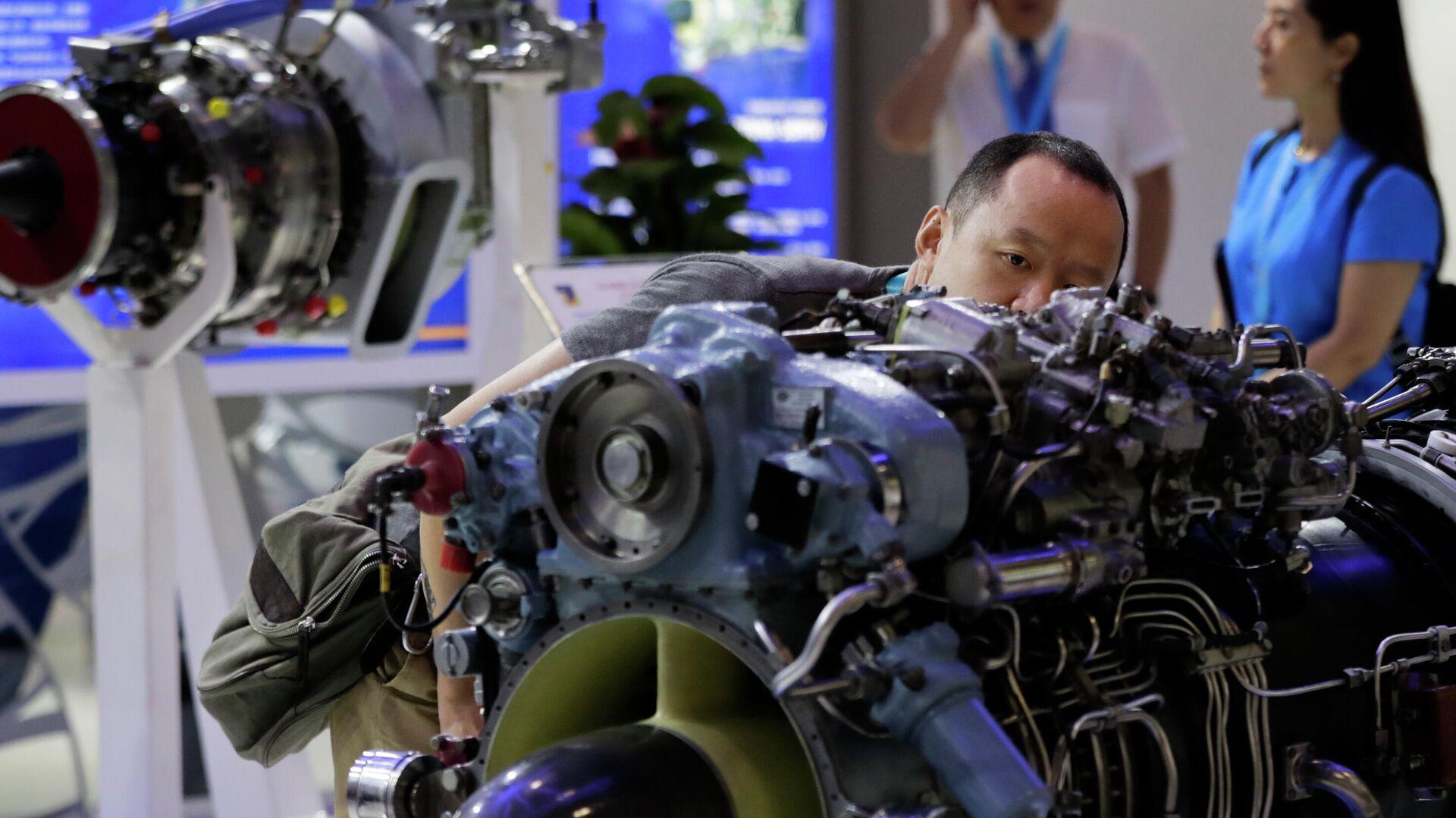 Мужчина рассматривает двигатель вертолета, разработанный компанией Мотор Сич, представленный на выставке Aviation Expo China в Пекине - РИА Новости, 1920, 07.12.2020