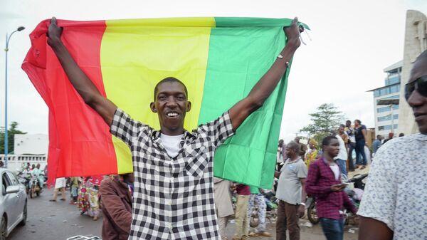 Мужчина с флагом в столице Мали Бамако