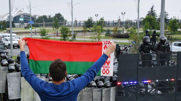 Сотрудники правоохранительных органов и участник акции протеста у Дворца независимости в Минске
