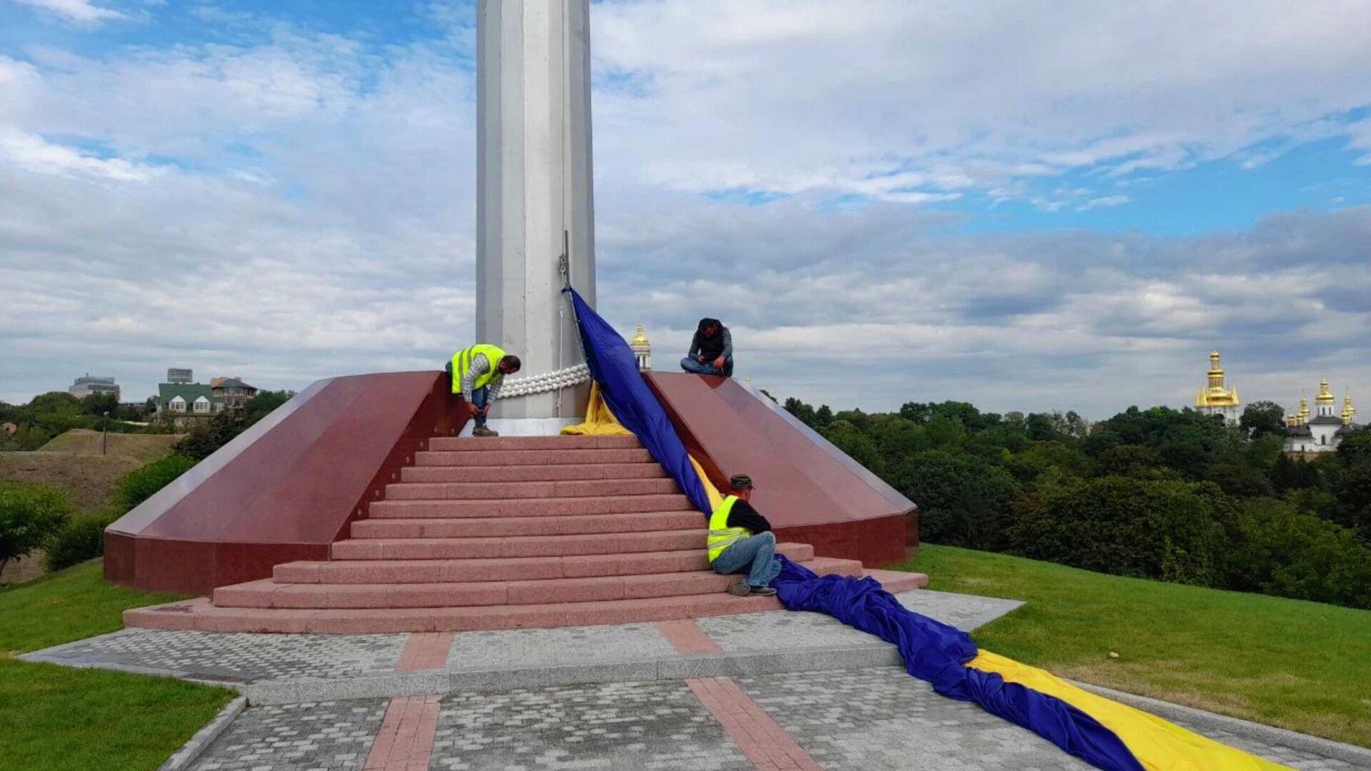 Сотрудники коммунальных служб снимают самый большой флаг Украины в Киеве - РИА Новости, 1920, 03.09.2021