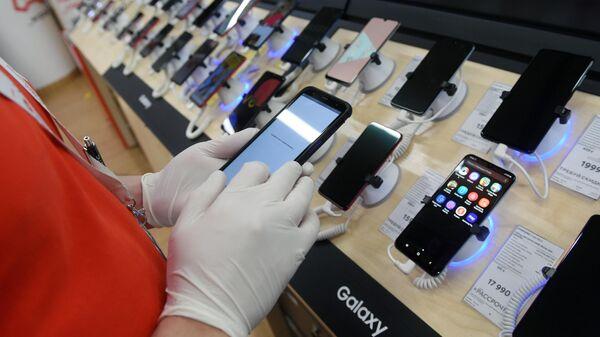 Сотрудник магазина М-видео держит в руках смартфон во время подготовки к открытию ТЦ Океания в Москве