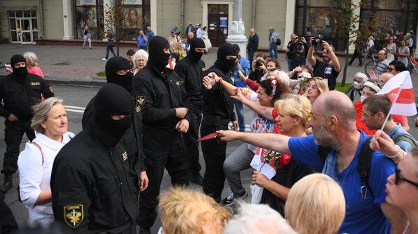 Участники акции протеста и сотрудники правоохранительных органов на проспекте Независимости в Минске