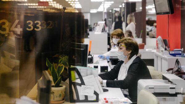 Сотрудники за работой в многофункциональном центре государственных и муниципальных услуг Мои документы