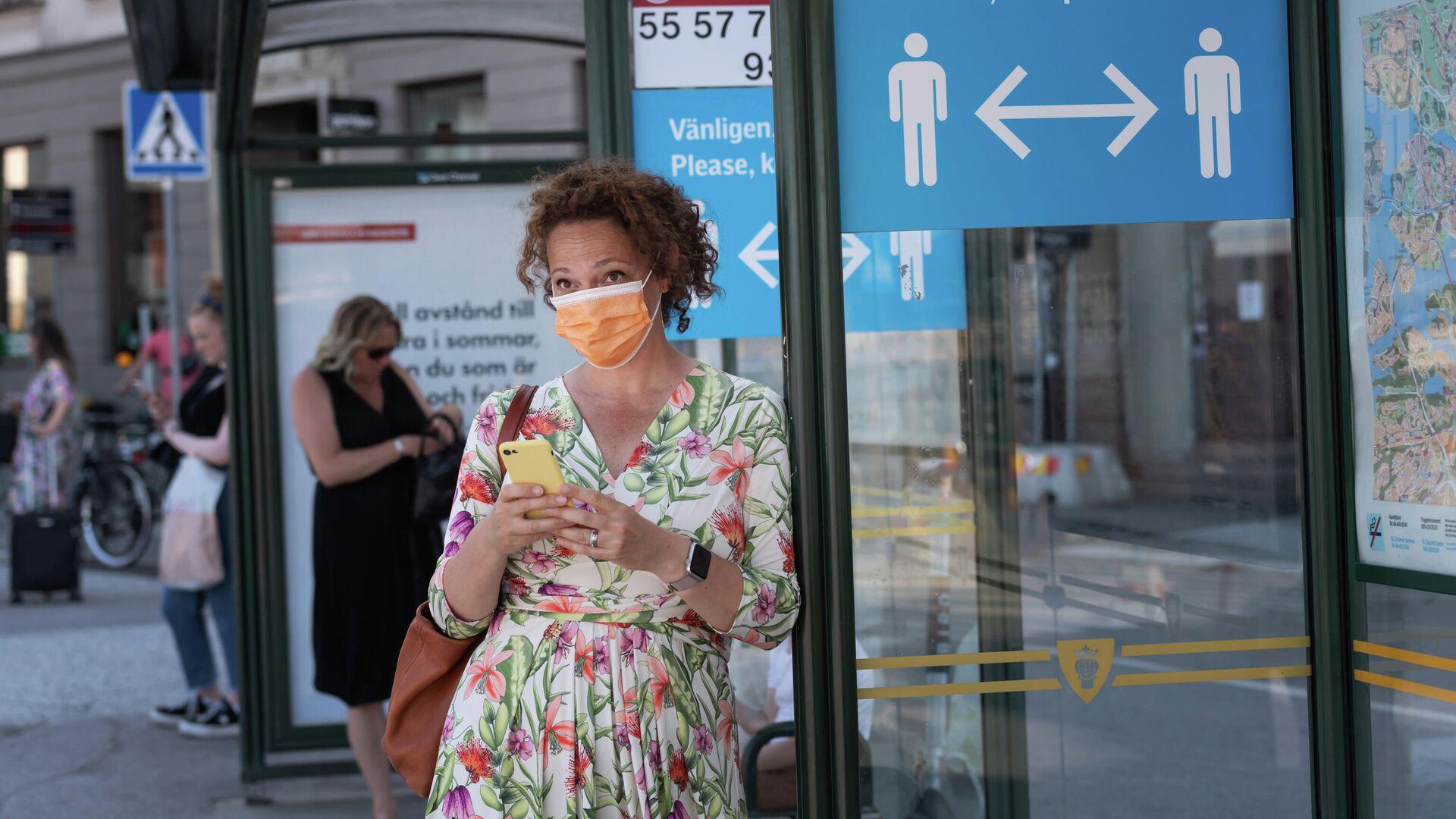 Женщина в защитной маске на автобусной остановке с плакатом, призывающим держать социальную дистанцию, Стокгольм, Швеция - РИА Новости, 1920, 01.09.2020