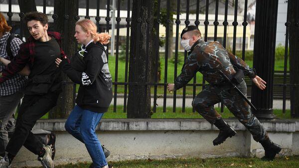 Сотрудник правоохранительных органов и участники акции протеста в Минске