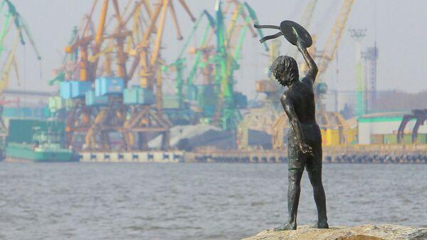 Памятник мальчику с бескозыркой и собакой, который провожает корабли в морском грузовом порту Клайпеды