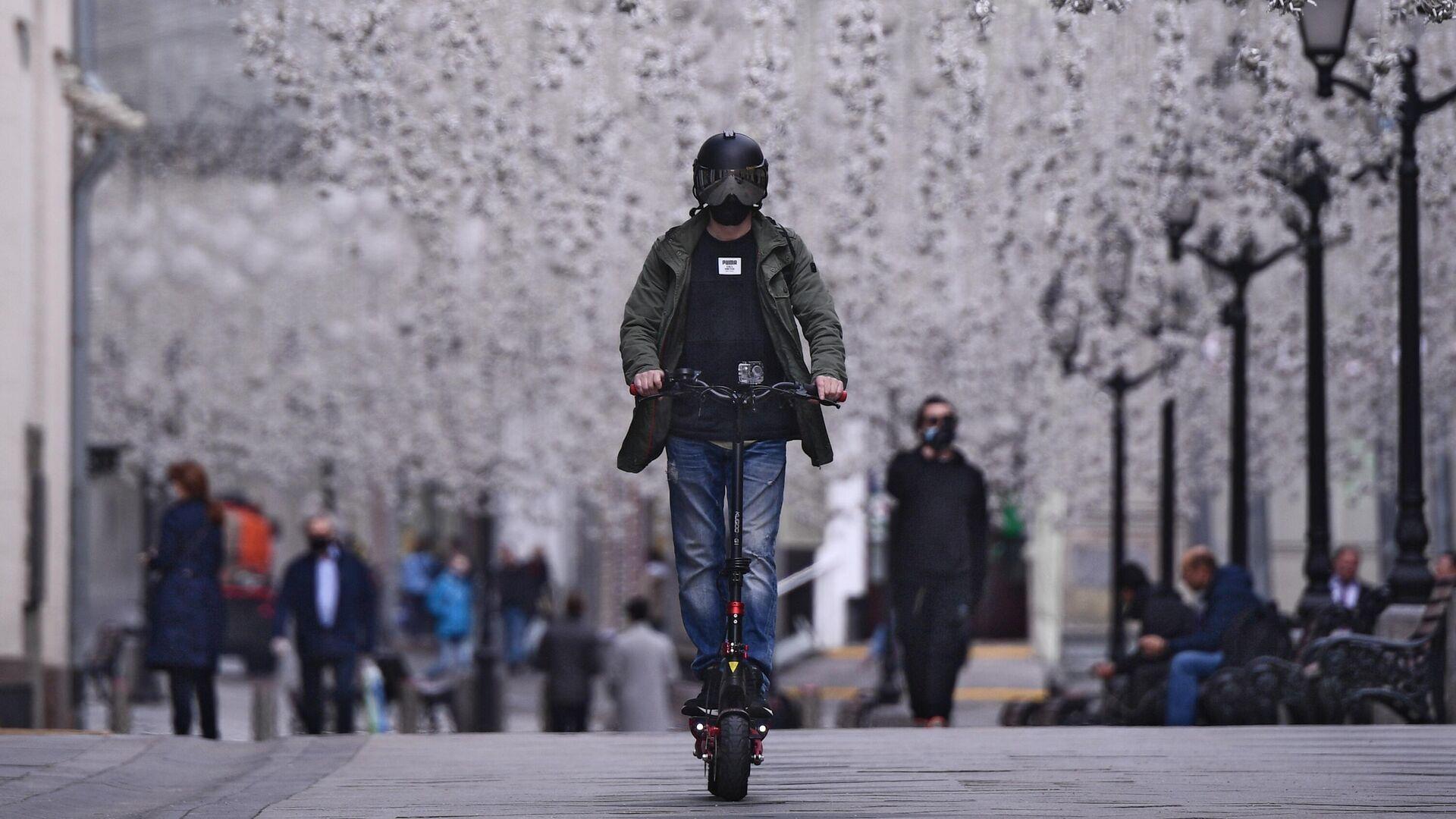 Мужчина в защитном шлеме катается на электросамокате - РИА Новости, 1920, 29.10.2020