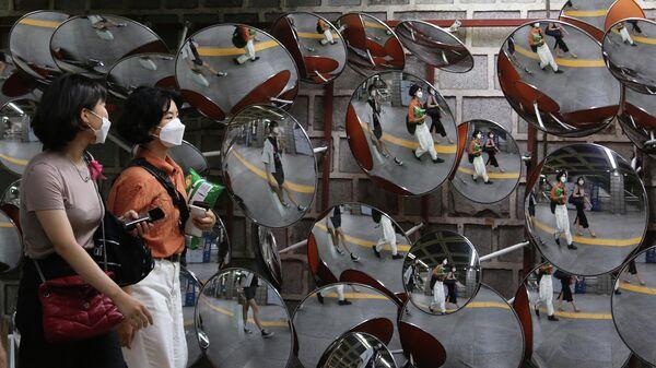 Женщины в защитных масках проходят мимо зеркал у станции метро в Сеуле
