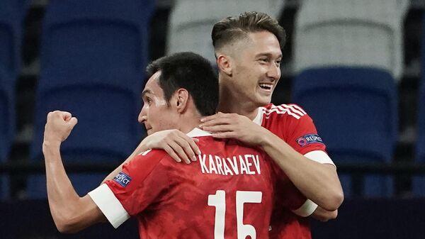 Футболисты сборной России Вячеслав Караваев (слева) и Антон Миранчук радуются забитому мячу