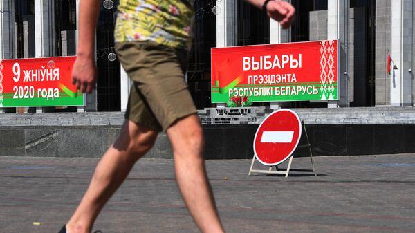 Мужчина перед избирательным участком на выборах президента Белоруссии в Минске