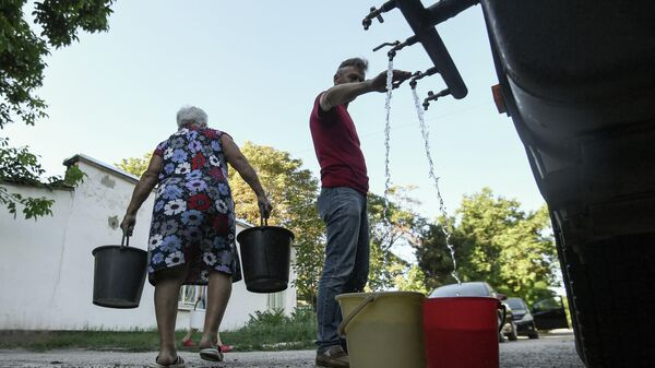Жители Cимферополя набирают в емкости питьевую воду, привезенную в цистернах