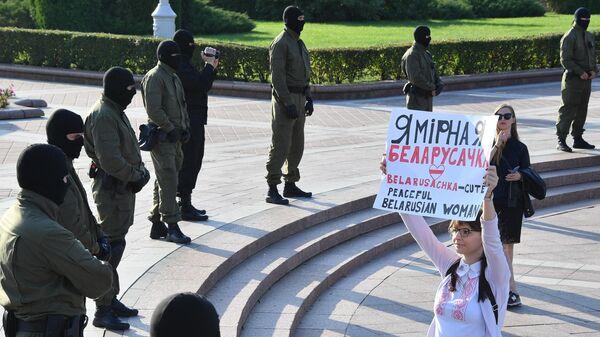Сотрудники правоохранительных органов и участница протестной акции женщин на площади Независимости в Минске