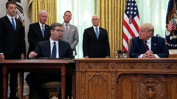Президент Сербии Александр Вучич и президент США Дональд Трамп во время церемонии подписания соглашения об экономическом сотрудничестве с премьер-министром Косова Авдулахом Хоти