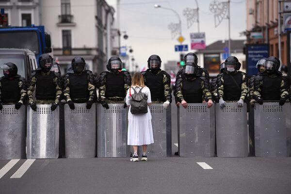 Участница несанкционированной акции оппозиции Марш единства и сотрудники милиции на улице в Минске