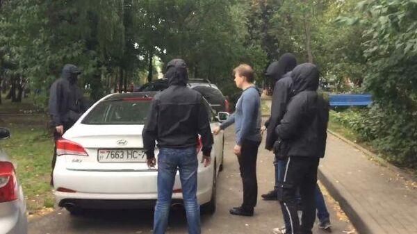 Белорусский оппозиционер Знак садится в машину в сопровождении неизвестных